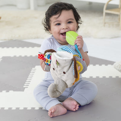 Baby playing with Skip Hop Banana Buddies Baby Elephant Puppet Book