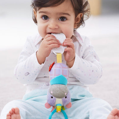 Baby teething on the Skip Hop Banana Buddies Chime & Teethe Toy in Unicorn