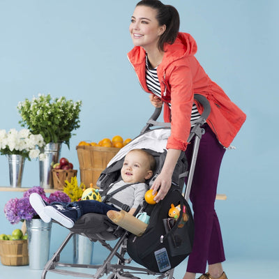 Baby sitting in a stroller with Skip Hop Grab & Go Stroller Saddle Bag in Black attached and items inside