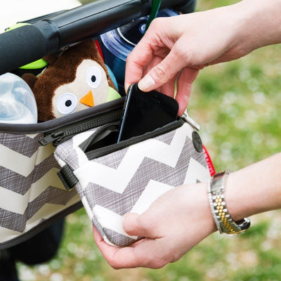 Mom placing cell phone in zippered pocket of Skip Hop Grab & Go Stroller Organizer in Chevron