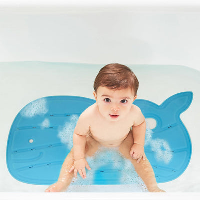 Toddler boy sitting on the Skip Hop Moby® Bath Mat in Blue