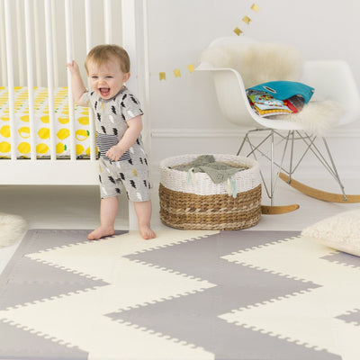 baby standing on Skip Hop Playspot Geo Triangular Interlocking Foam Floor Tiles in Grey and Cream