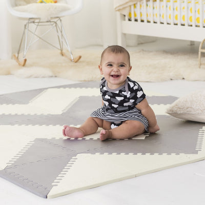 baby sitting on Skip Hop Playspot Geo Triangular Interlocking Foam Floor Tiles in Grey and Cream