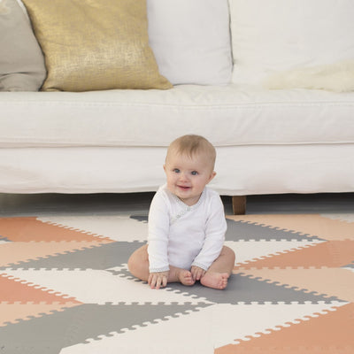 baby sitting on Skip Hop Playspot Geo Triangular Interlocking Foam Floor Tiles in Grey and Peach