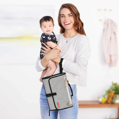 Mom holding baby and Skip Hop Pronto! Changing Station in Grey Melange