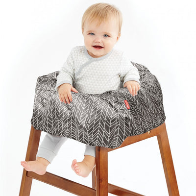 Baby sitting in high chair with Skip Hop Take Cover Shopping Cart & High Chair Cover in Grey Feather