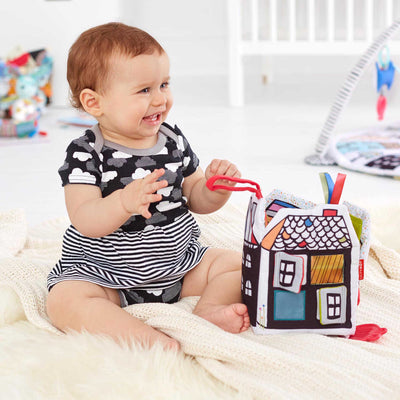 Baby playing with Skip Hop Vibrant Village Peek & Play Activity Book