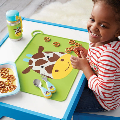 Girl eating with Skip Hop Zoo Fold & Go Silicone Placemat in Giraffe