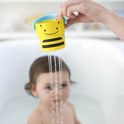Girl playing in the bath with Skip Hop Zoo Stack & Pour Buckets
