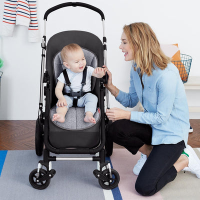 Baby sitting in stroller on Skip Hop Stroll & Go Cool Touch Stroller Liner in Heather Grey