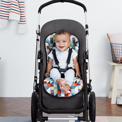 Baby sitting in stroller on Skip Hop Stroll & Go Cool Touch Stroller Liner in Prism