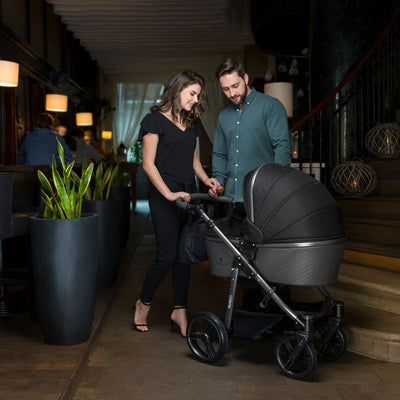 Mom pushing the Venicci Carbo Lux 2 in 1 Stroller in Black