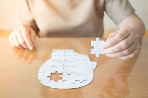 Person putting together puzzle of head
