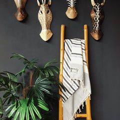 Striped towel hanging on bamboo rack with green plants and wall decor