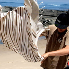 Man with EKZO shirt and hat shaking brown striped towel on the beach