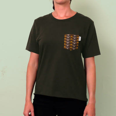 Woman wearing dark green t-shirt with gold and gray chest pocket