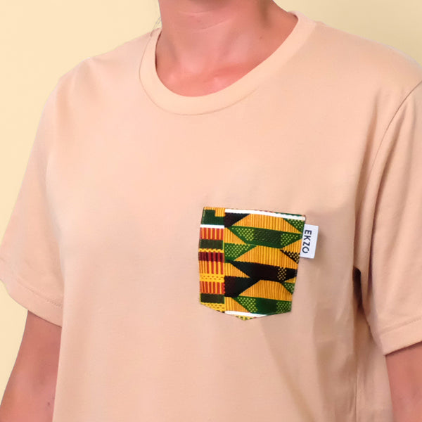 Close-up of African wax fabric chest pocket on tan t-shirt