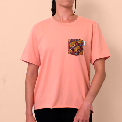 Woman wearing a salmon colored t-shirt with gold and maroon patterned chest pocket