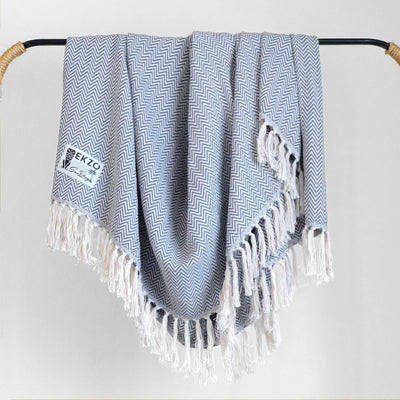 Blue and white blanket with white tassels hanging on rack