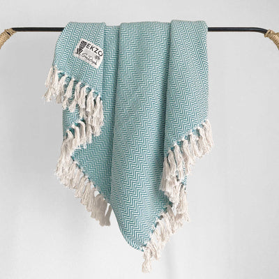 Green and white woven blanket with white tassels hanging on rack