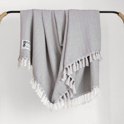 Gray and white woven blanket with white tassels hanging on rack