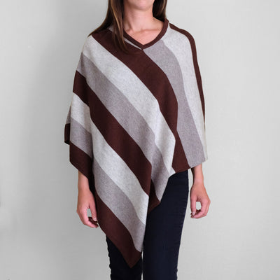 Woman wearing white gray and brown striped poncho