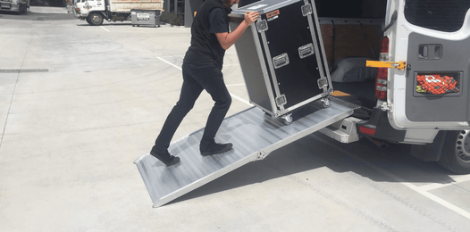 Person walking up a aluminium van ramp with large sound equipment box