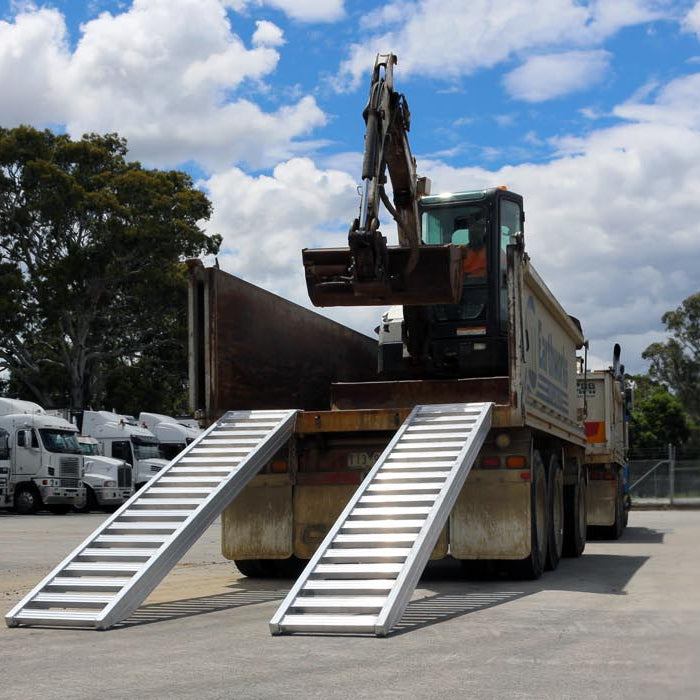 Image of an excavator loading a Heeve excavator ramp attached on a truck