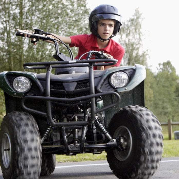 young man wearing helmet riding ATV on a road