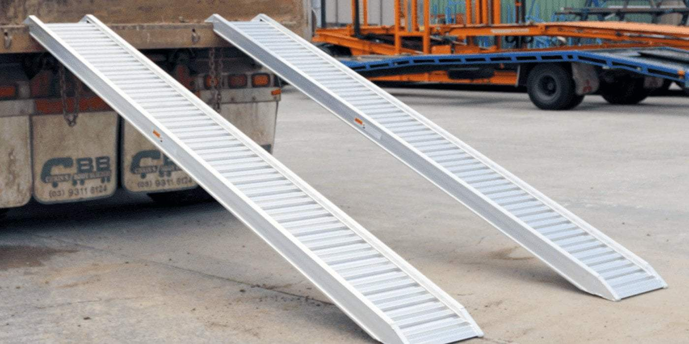 pair of loading ramps attached to a vehicle in a construction site