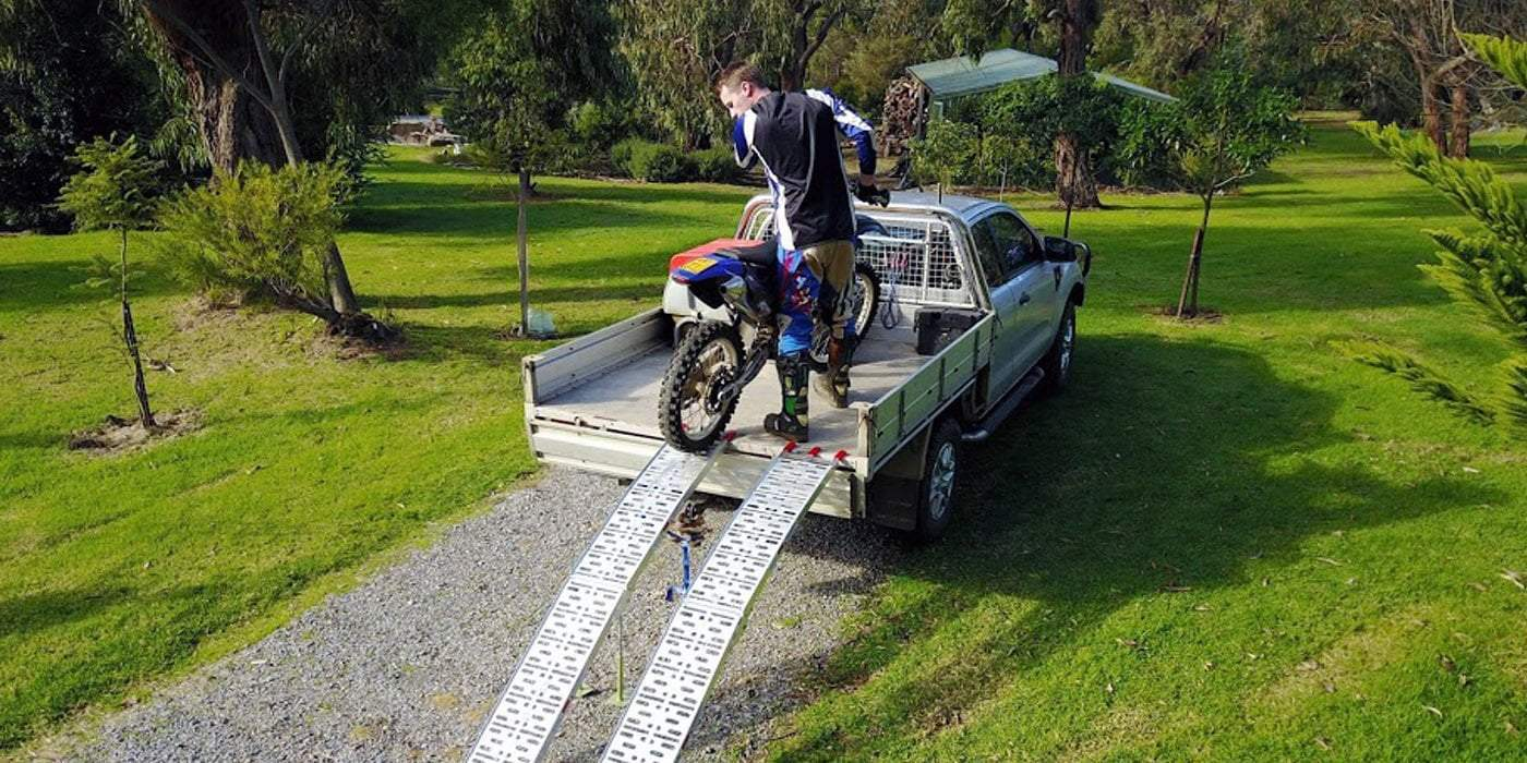 motorcycle rider and a bike on trailer truck with ramp