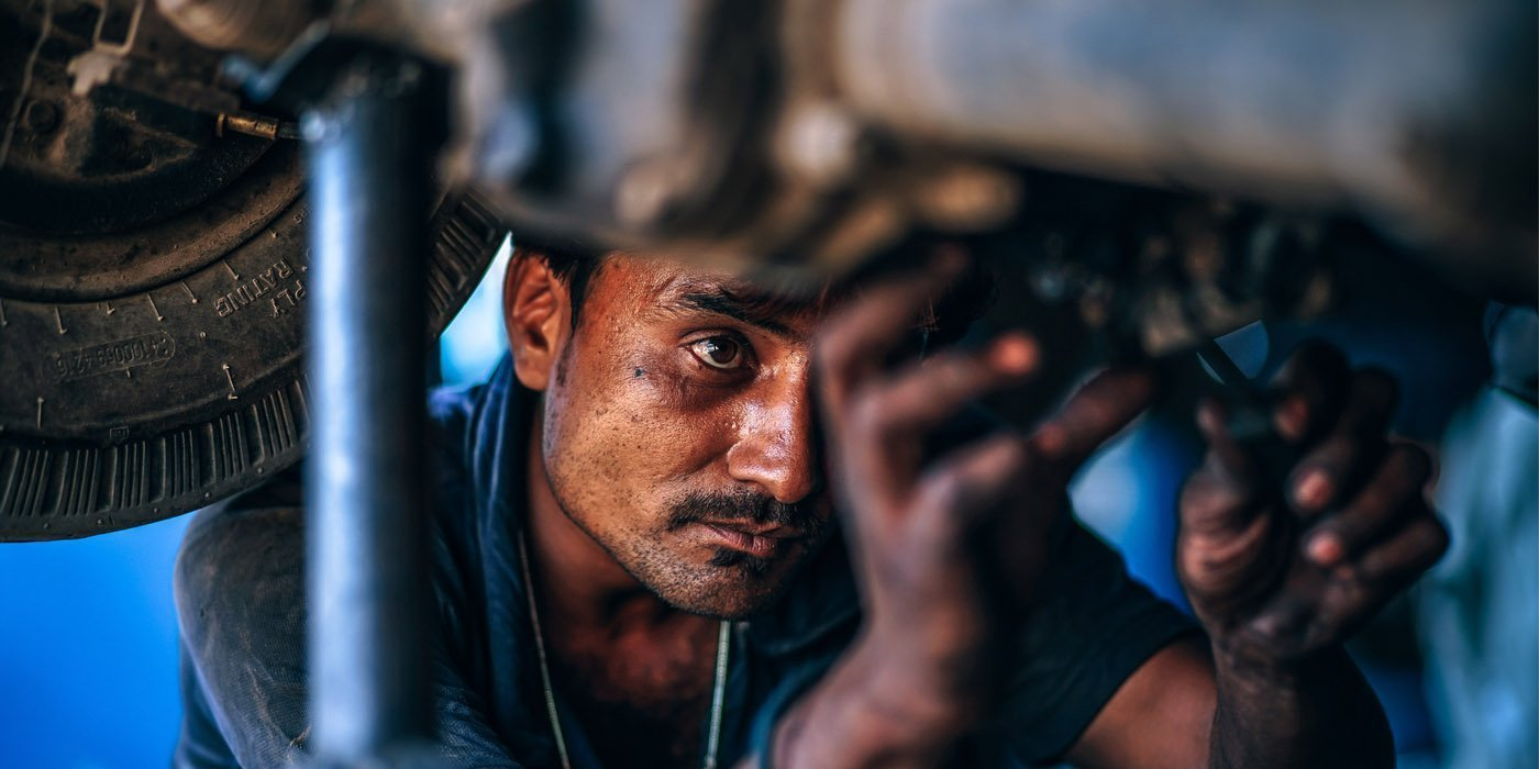auto mechanic doing repair on a raised vehicle
