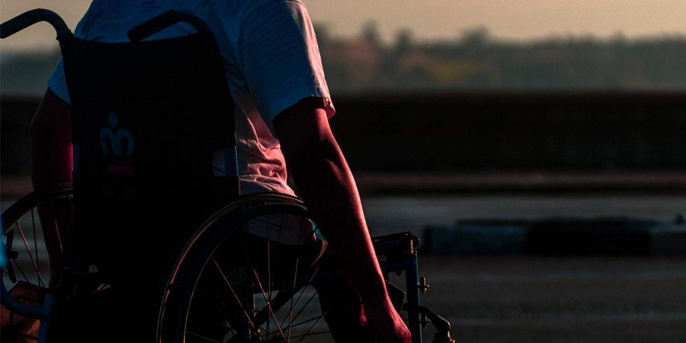 a man riding his wheelchair on a road during late afternoon