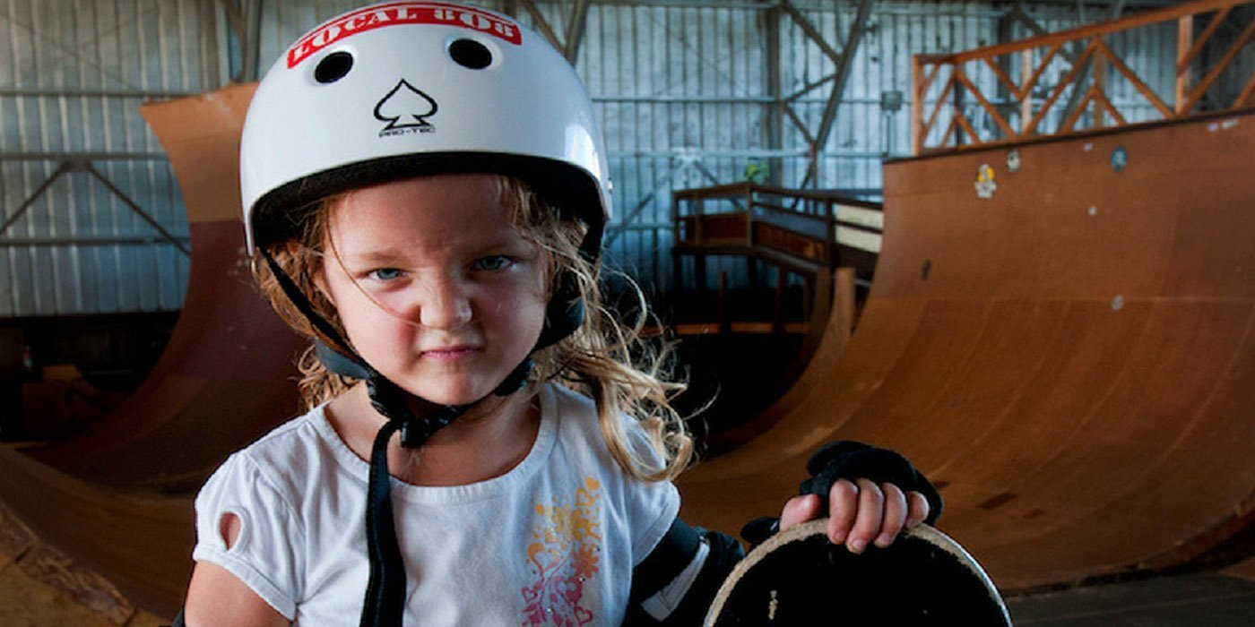 A young girl wearing helmet and holding a skateboard at a skateboard park