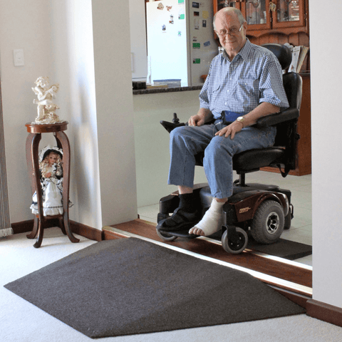 Old man on his mobility scooter facing a doorway with ramp