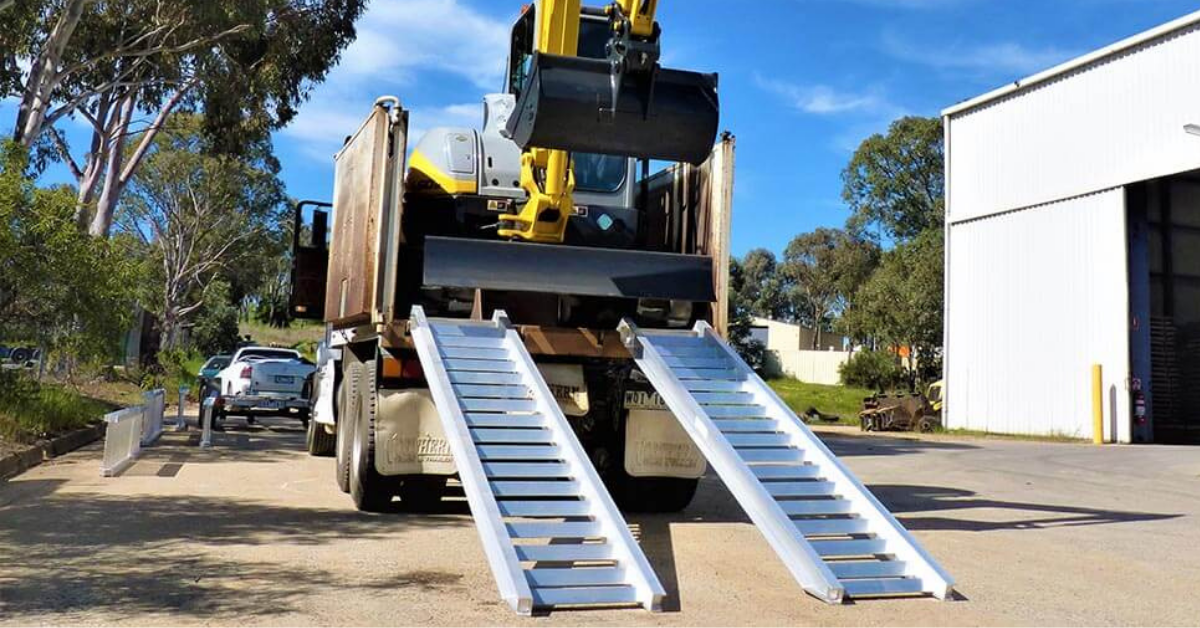 Image of machinery loading ramps attached at the rear of a truck with an excavator ready to unload