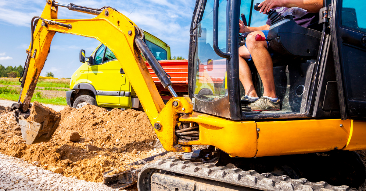 An image of a mini excavator operated by a man