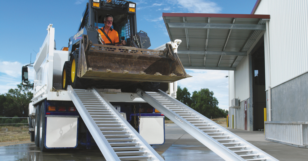 Image of a skid steer unloading from the rear of a truck using a pair of loading ramps