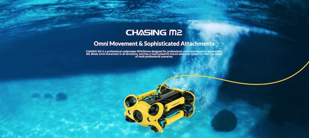 Chasing M2 Under Water Drone for Sale image. Yellow Chasing M2 Underwater Drone with yellow tether exploring in clear, bright blue water.