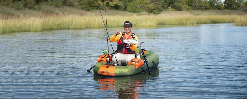 Sea Eagle PackFish7 1 Person Inflatable Fishing Boat for Sale is being operated by 1 guy and he is showing off his catch. The inflatable packraft for sale is hunter green and orange.