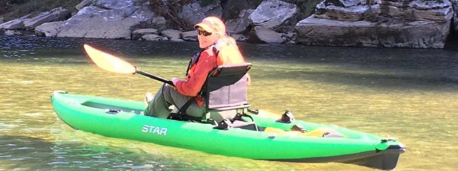 Star Pike Inflatable Fishing Kayak Review. Women sitting down paddling the sit on top fishing kayak down the river.