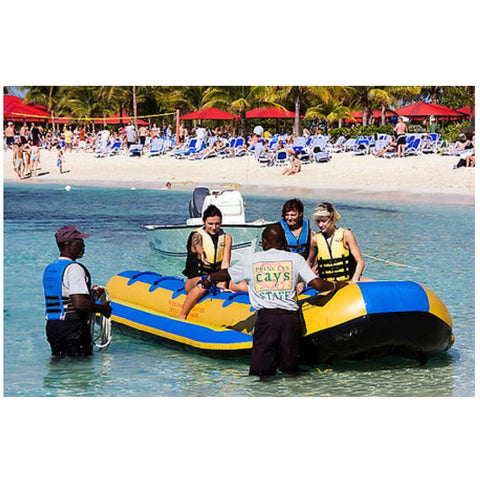 Passengers being assisted boarding the Island Hopper 12 Person Towable Banana Boat Taxi in the ocean.