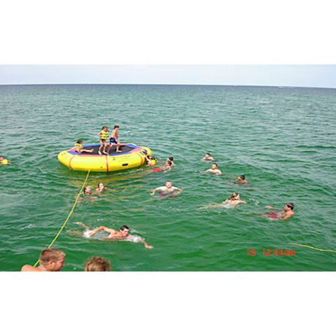Kids playing in and around the Island Hopper 13' Bounce N Splash Inflatable Water Bouncer in the ocean.