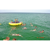 Image of Kids playing in and around the Island Hopper 13' Bounce N Splash Inflatable Water Bouncer in the ocean.