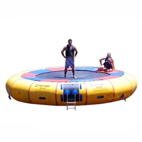 Island Hopper 20ft Acrobat Water Trampoline on a white background with 1 man standing on the black water trampoline surface and 1 girl sitting on the thin red and blue pad that is connected to the yellow inner tube.