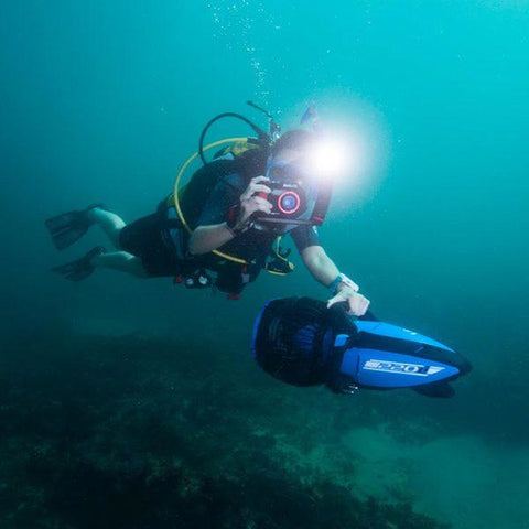 Yamaha 220Li Sea Scooter in use by a scuba diver with 1 hand taking a picture and 1 hand on the Yamaha 220Li Sea Scooter handle.