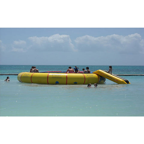 Yellow Island Hopper 25ft Giant Jump Water Trampoline on the ocean with several people on it.  Bounce N Slide attachment also in use.
