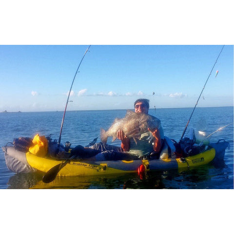 Yellow Advanced Elements StraitEdge Angler Solo Inflatable Kayak with grey highlights.  Fishing poles attached.