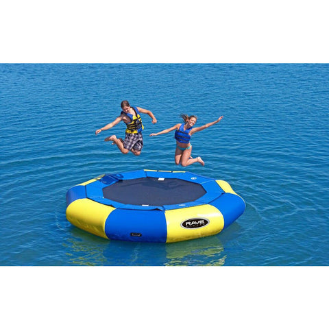 2 girls jumping on the Rave Aqua Jump 120 Eclipse Water Trampoline on the lake.  Panels alternate between yellow and blue around the water trampoline.  Thin blue pad inner ring over the connection to the black water trampoline surface.  Black Rave logo on one of the yellow panels.