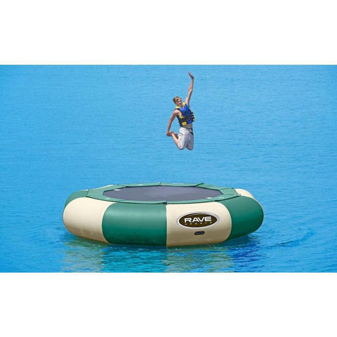 A guy jumping on a green and tan Rave Aqua Jump Eclipse 150 Northwoods Water Trampoline on the lake.